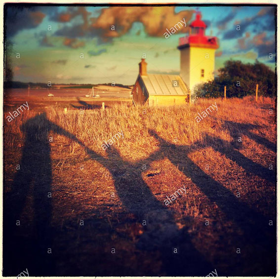 Family shadows in front of lighthouse in Agon, France stock photography