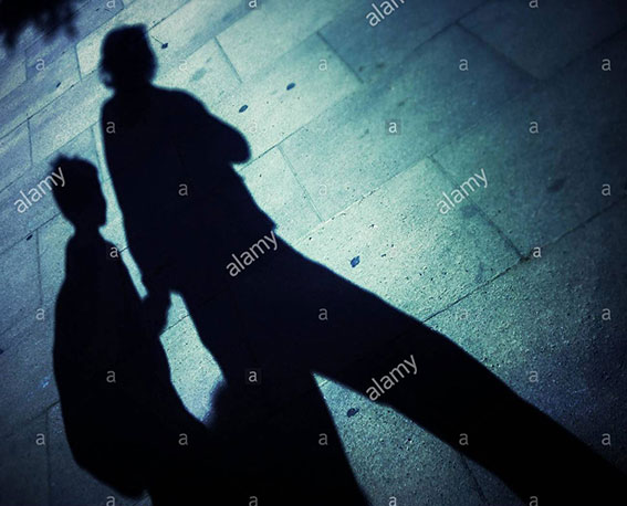 Shadow of a mother and her child walking together on the street in Barcelona stock photography