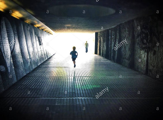 Silhouettes walking through a dark under pass simbolizing light at the end of the tunnel stock photography