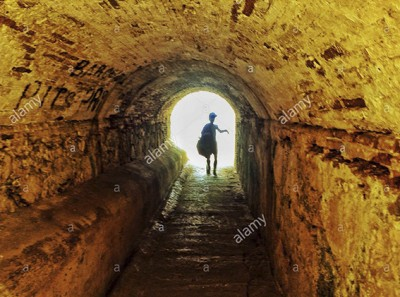 Silhouette of a teenager walking through a dark underpass symbolizing light at the end of the tunnel © Queralt Sunyer