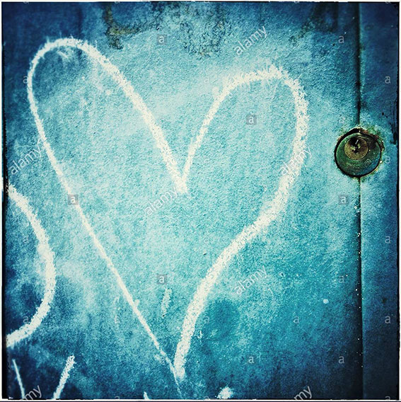 A love heart painted in chalk and a padlock in a blue door stock photography