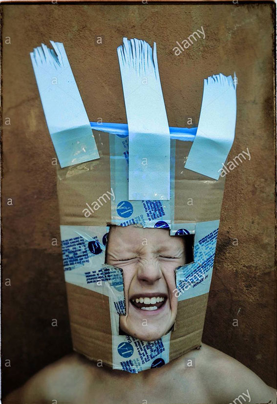 Boy playing with a carton box mask stock photography