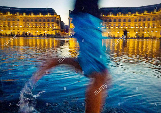 Boy running in fountain in Place de la Bourse in Bordeaux, France stock photography