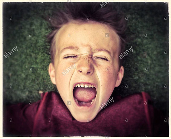 Close up of a boy, screaming loudly with eyes closed. Boy excited and happy stock photography