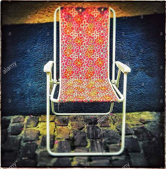 Empty plastic beach chair sitting alone on cobbled street in Alsace, France stock photography