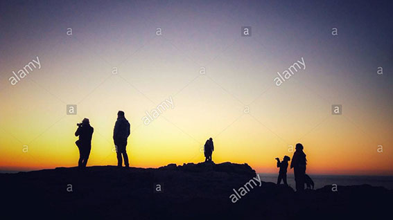 Family tourists silhouetted against sunset ar the Pointe du Raz, Plogoff, France, Europe stock photography