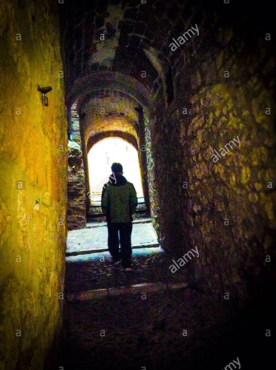 Single silhouette walking through a dark alley in the Call (jewish quarter), Girona, Catalonia stock photography