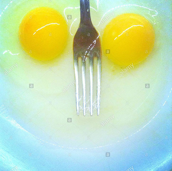 Smile on objects. A pair of eggs and a fork stock photography