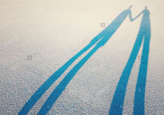Long shadow of a couple lovers holding hands stock photography