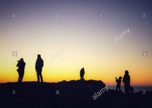 Family tourists silhouetted against sunset ar the Pointe du Raz, Plogoff, France, Europe © Queralt Sunyer