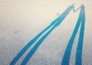 Long shadow of a couple lovers holding hands © Queralt Sunyer